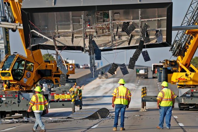 Work continues as a message board on Westbound I-70 west of Emerson waits to be removed after a dump truck hit it, Friday, Sept. 21, 2018.  The highway will remain closed during the clean-up for hours.