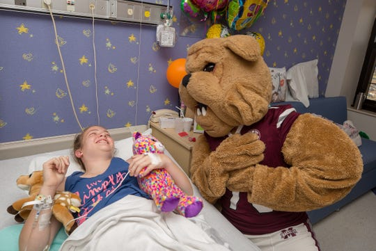 """Malorie Franovich of Pascagoula shares a laugh with Bully during the Mississippi State football team's visit to Children's Hospital in July. Dodd came out of """"retirement"""" to become Bully for the patients that day."""