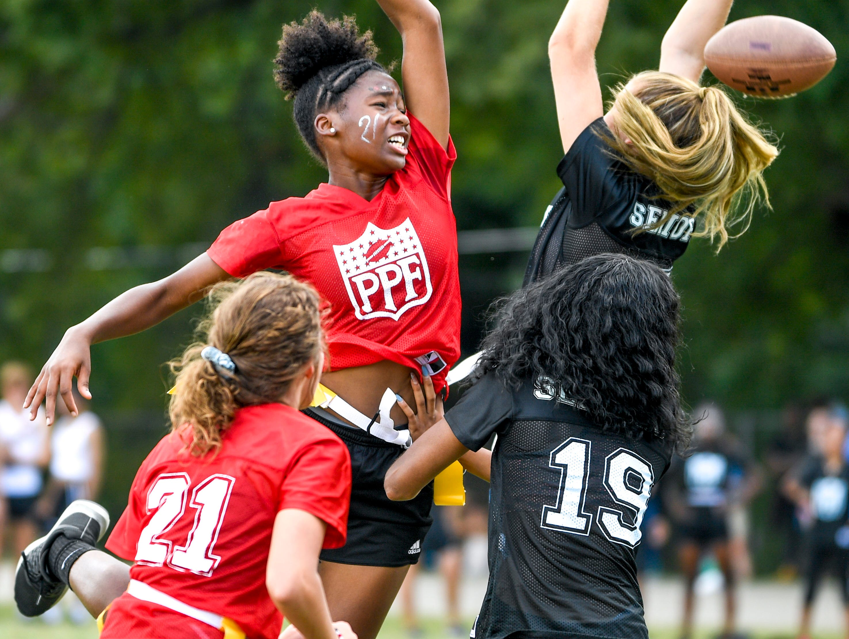 Sophomore and senior players leap to catch a pass thrown for a sophomore during the 2017 Powder Puff game at Madison Academic High School in Jackson, Tenn., on Friday, Sept. 21, 2018.