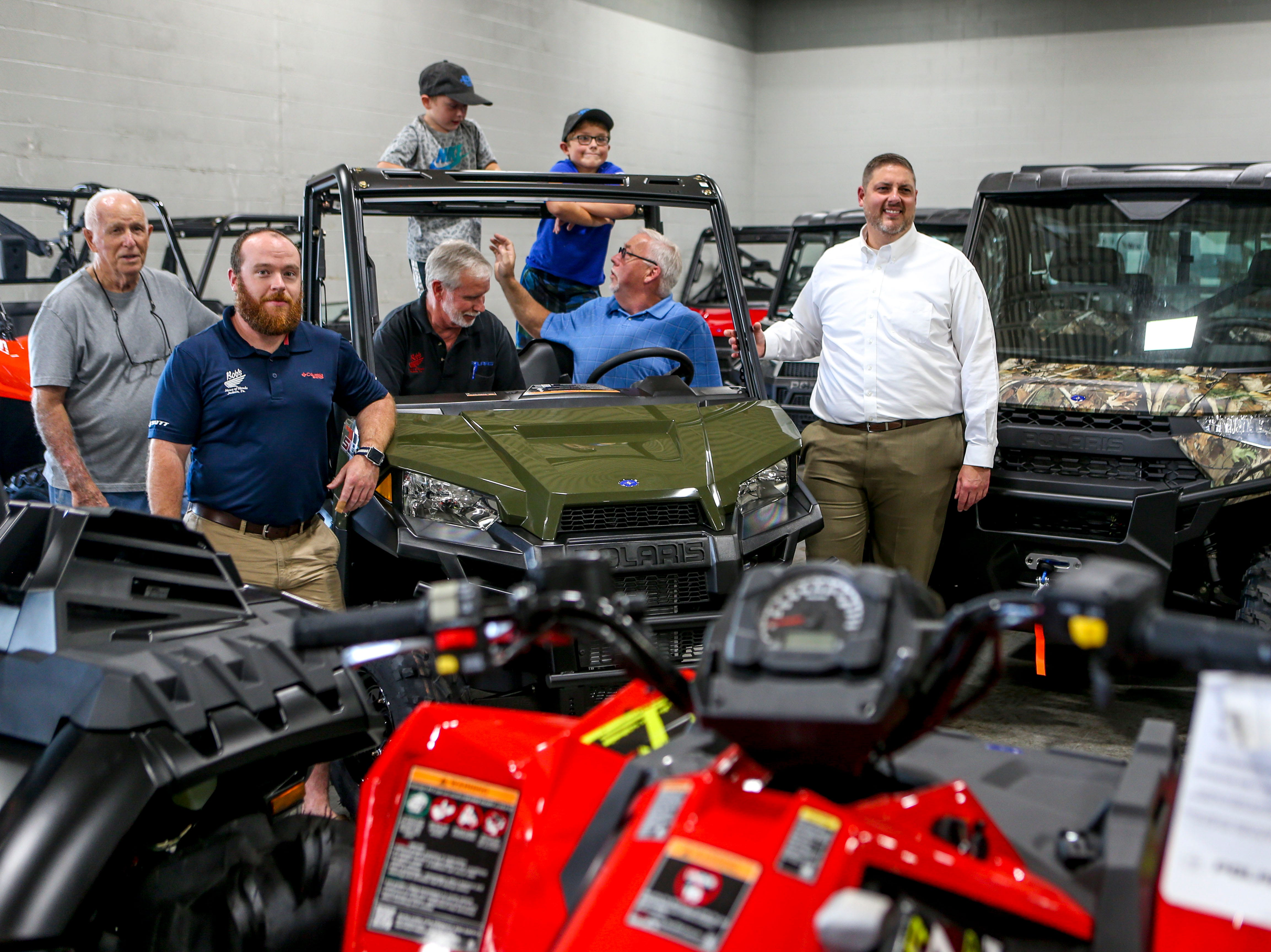 All three owners of Bob's House of Honda, the winner of the ATV John Coleman, center, Coleman's grandsons John Patrick Coleman, 4, and Bradley Coleman, 8, and John Miller, CEO of Lifeline Blood Services, right, pose with a model of the Polaris ATV given away in a contest at Bob's House of Honda in Jackson, Tenn., on Thursday, Sept. 20, 2018.