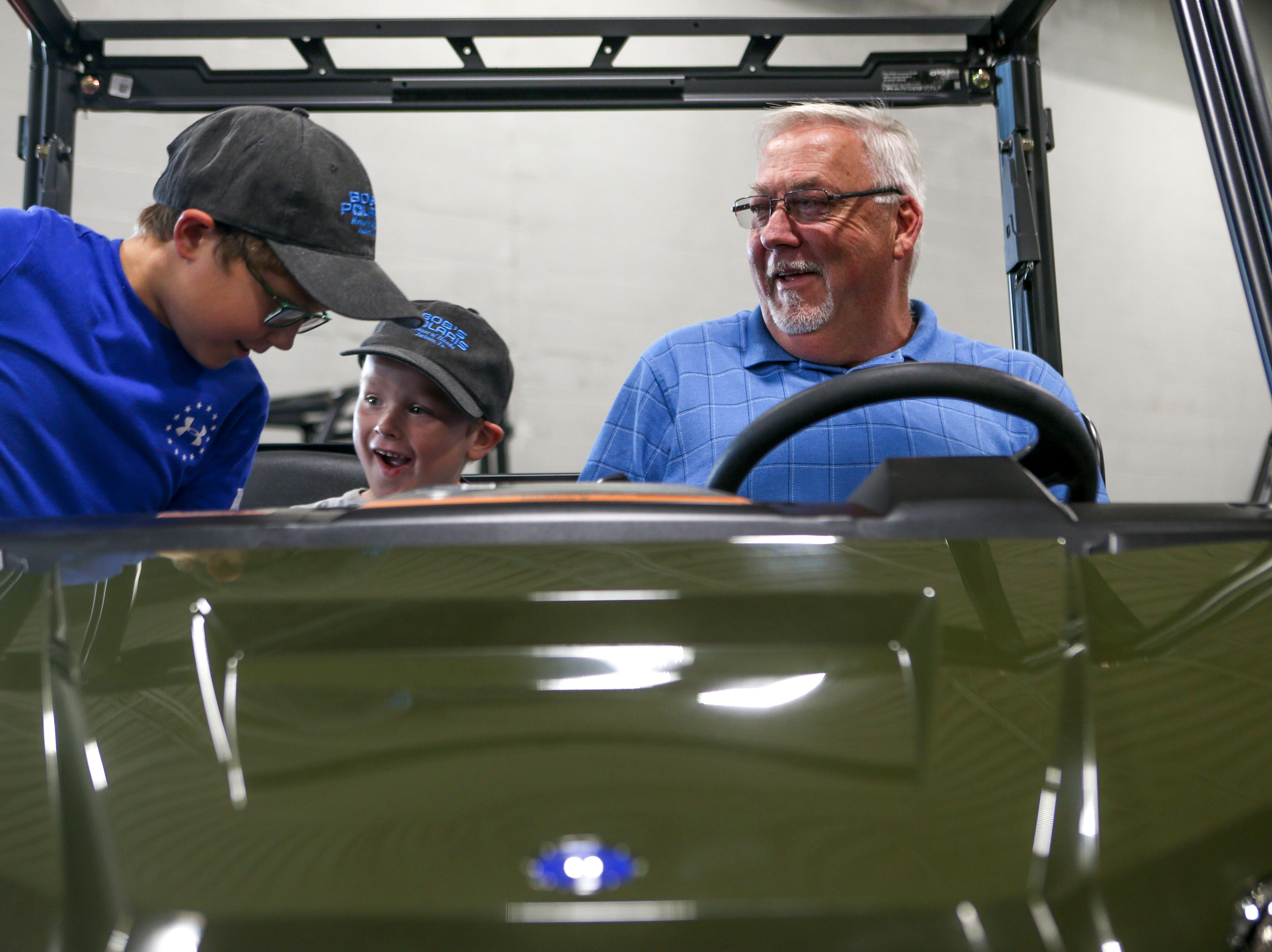 John Patrick Coleman, 4, center, and his brother Bradley Coleman, 8, left, jump up to join their grandfather John Coleman, right, seated in a model Polaris after Coleman won an ATV in a contest with Lifeline Blood Services at Bob's House of Honda in Jackson, Tenn., on Thursday, Sept. 20, 2018.