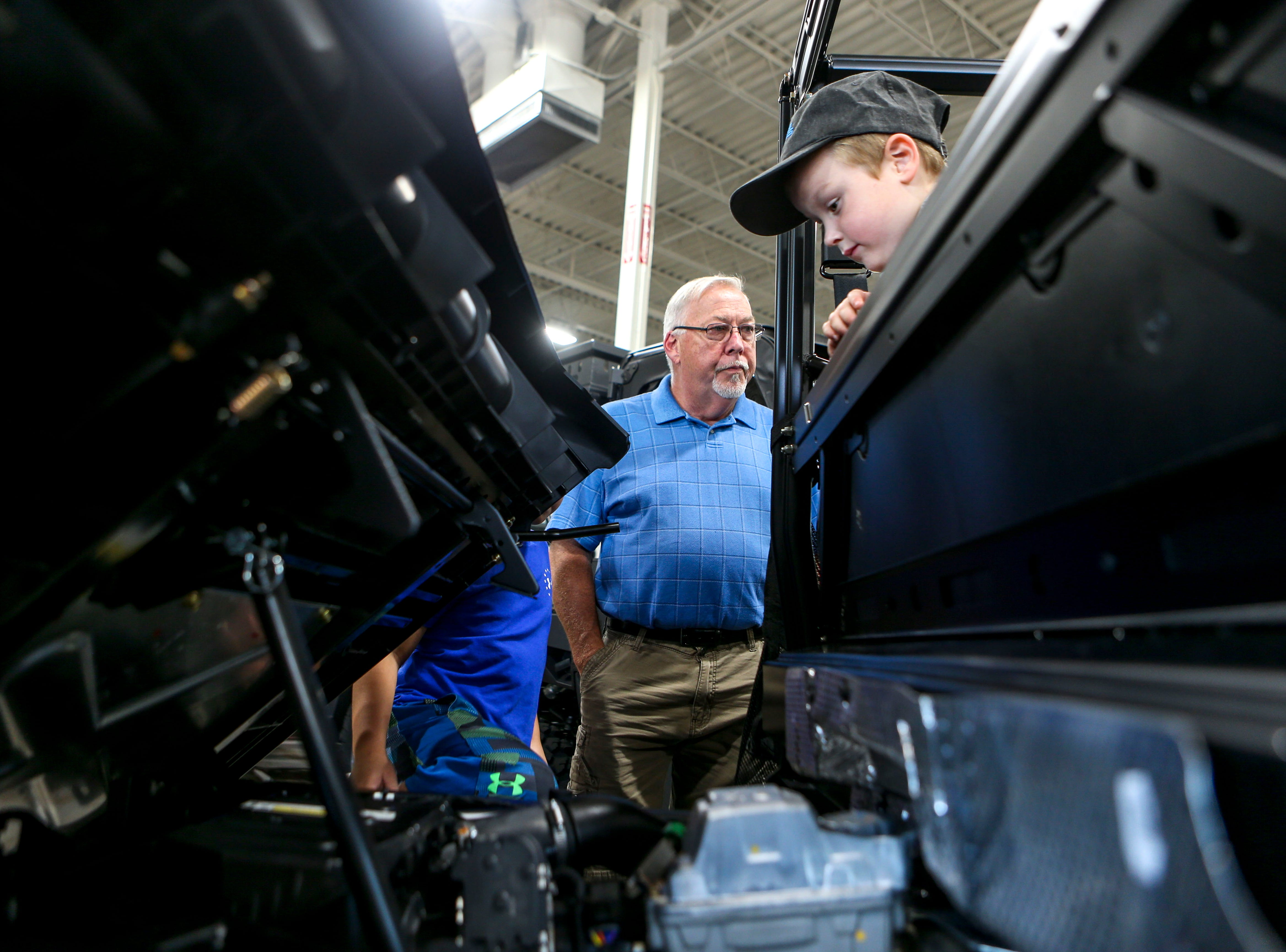 John Patrick Coleman peers into the engine compartment of a Polaris ATV as Bob Beasley provides a run down of the vehicle at Bob's House of Honda in Jackson, Tenn., on Thursday, Sept. 20, 2018.