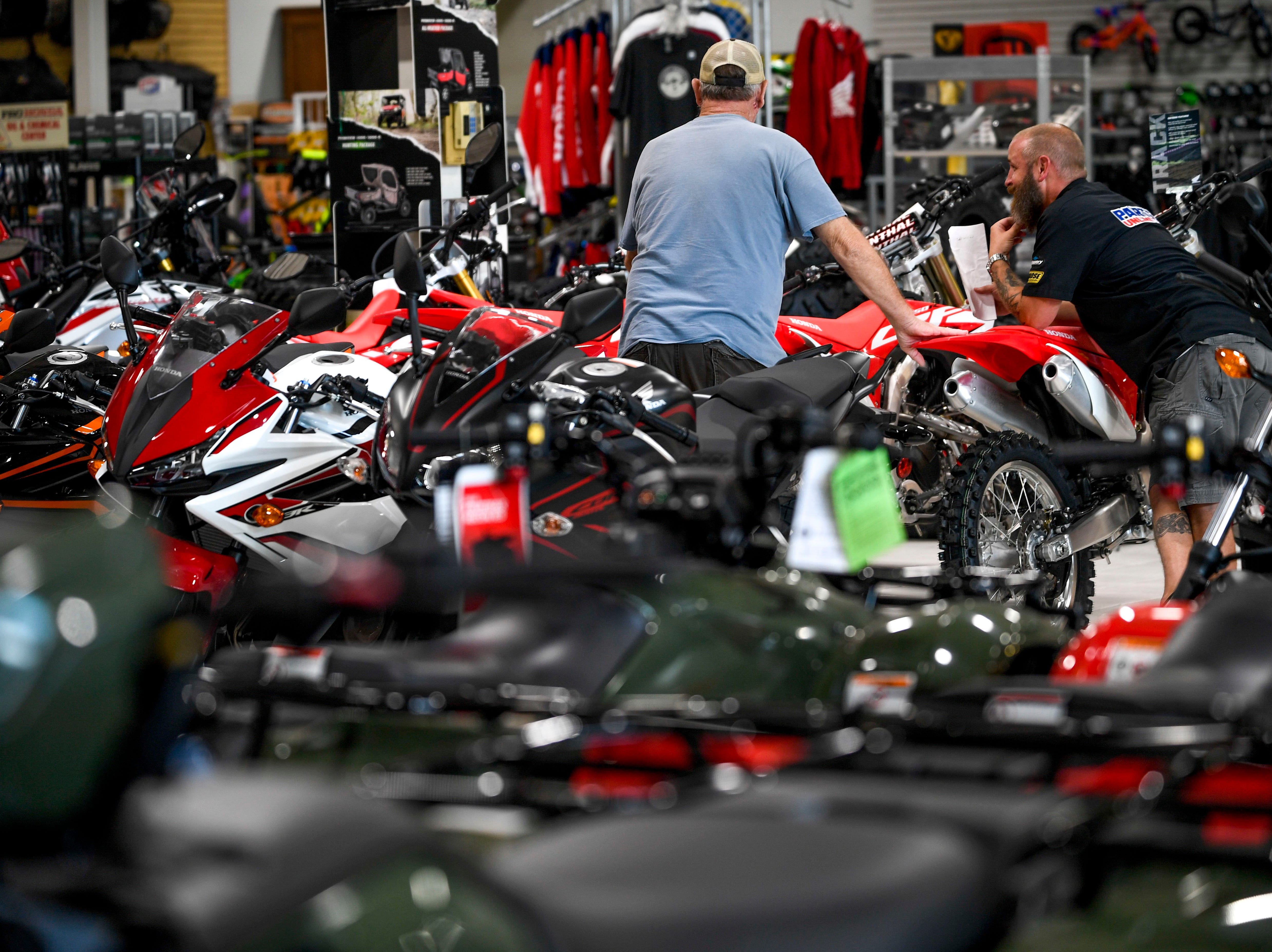 Customers look over ATVs at Bob's House of Honda in Jackson, Tenn., on Thursday, Sept. 20, 2018.