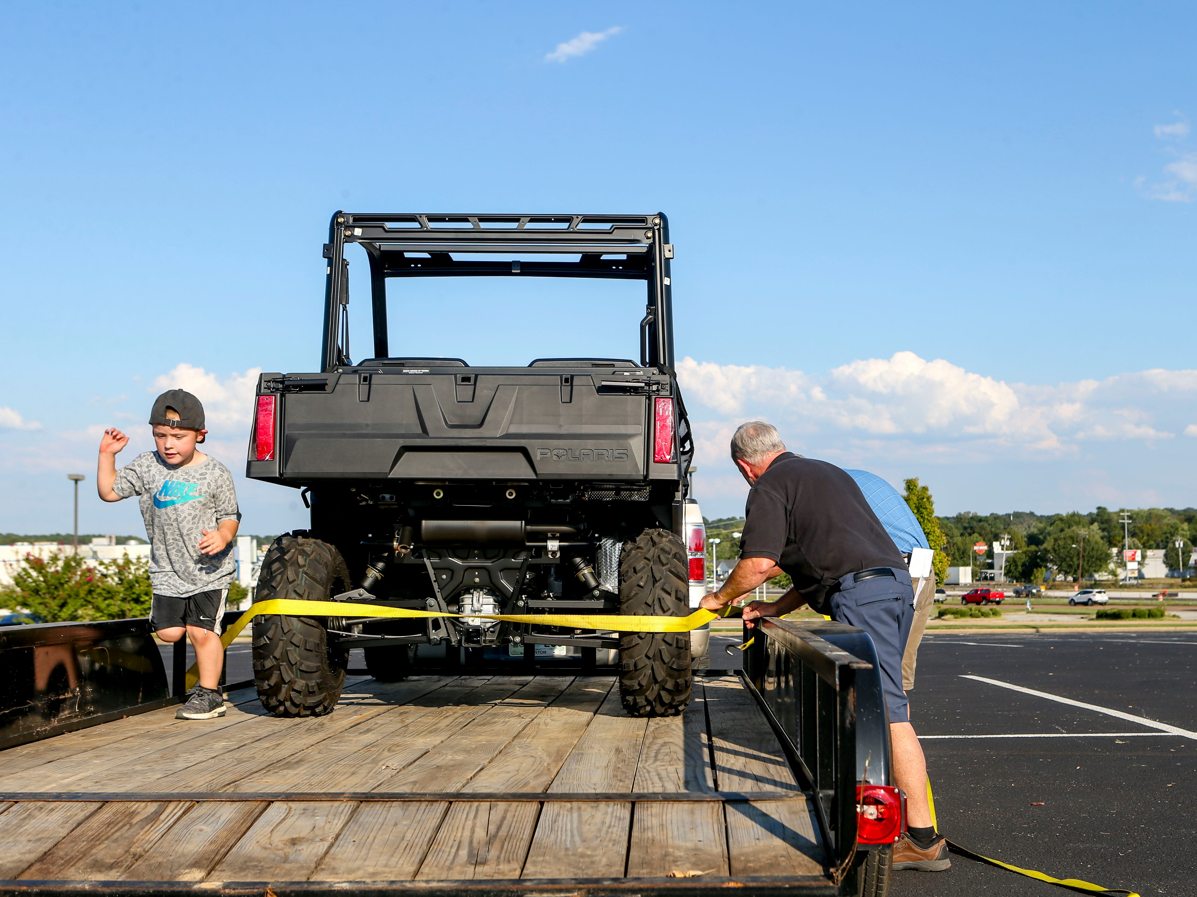 John Patrick Coleman, 4, left, runs around on top of the trailer while Bob Beasley and John Coleman, right, tighten down straps at Bob's House of Honda in Jackson, Tenn., on Thursday, Sept. 20, 2018.