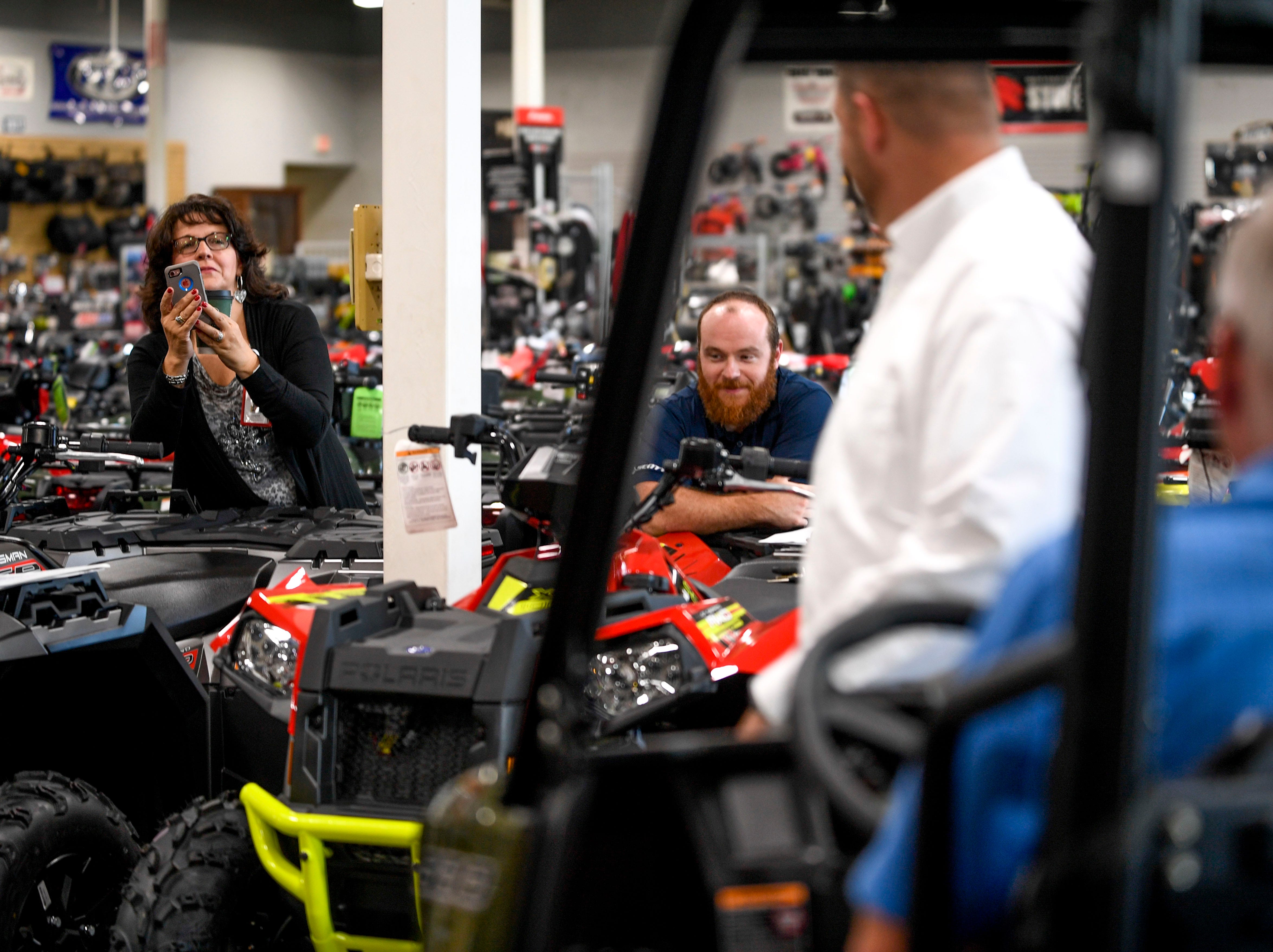 Cherie Parker, the public relations coordinator for Lifeline Blood Services, adjusts those involved in the ATV giveaway  at Bob's House of Honda in Jackson, Tenn., on Thursday, Sept. 20, 2018.