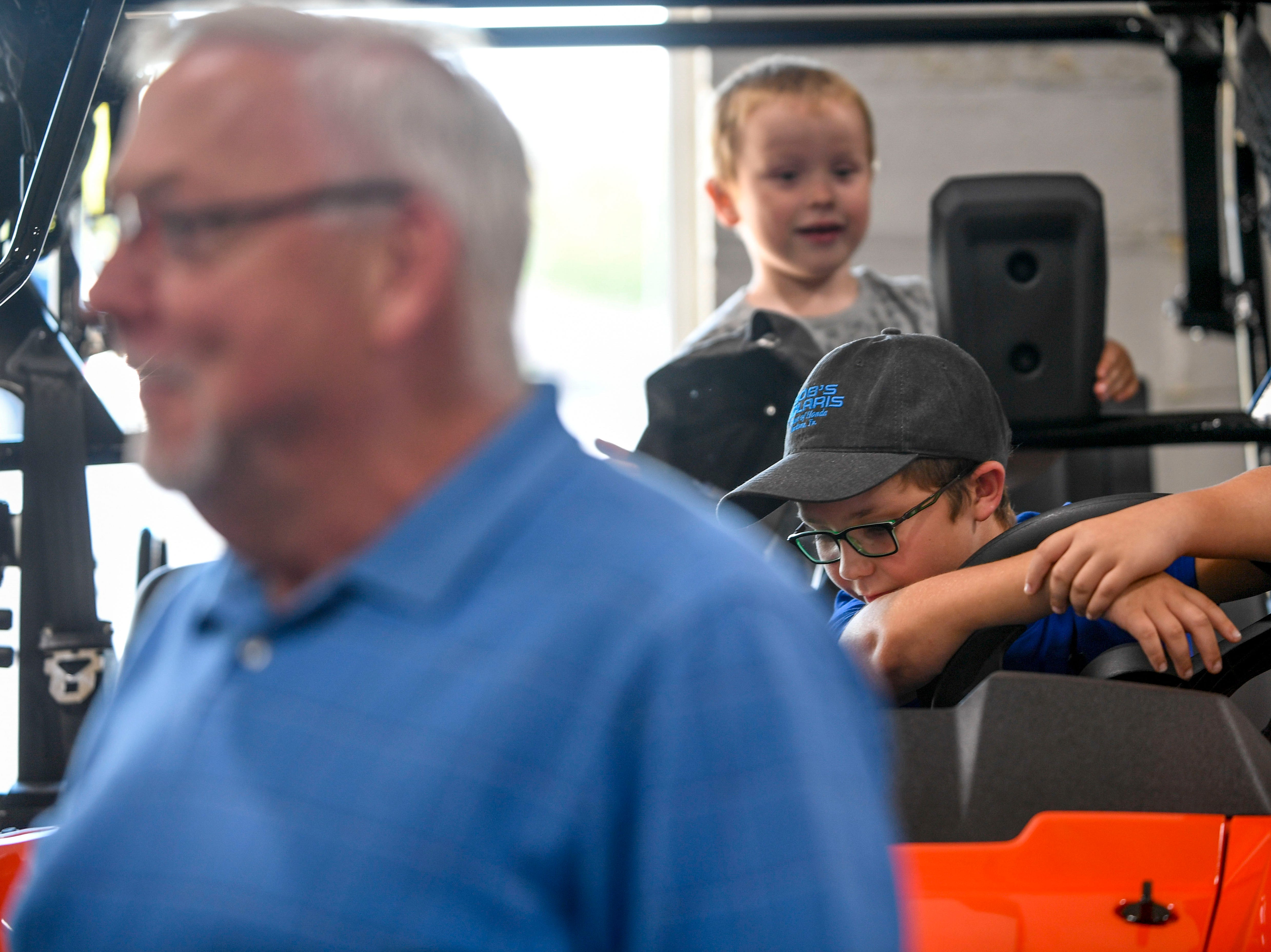 Bradley Coleman, 8, right, and his brother John Patrick Coleman, 4, background, explore other ATVs while their grandfather speaks to owners at Bob's House of Honda in Jackson, Tenn., on Thursday, Sept. 20, 2018.