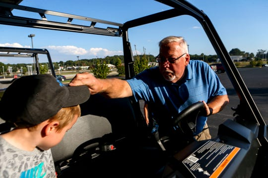 John Coleman, right, places a baseball cap onto his grandson, John Patrick Coleman, 4, left, while they sit in the new ATV the family won from a contest at Bob's House of Honda in Jackson, Tenn., on Thursday, Sept. 20, 2018.