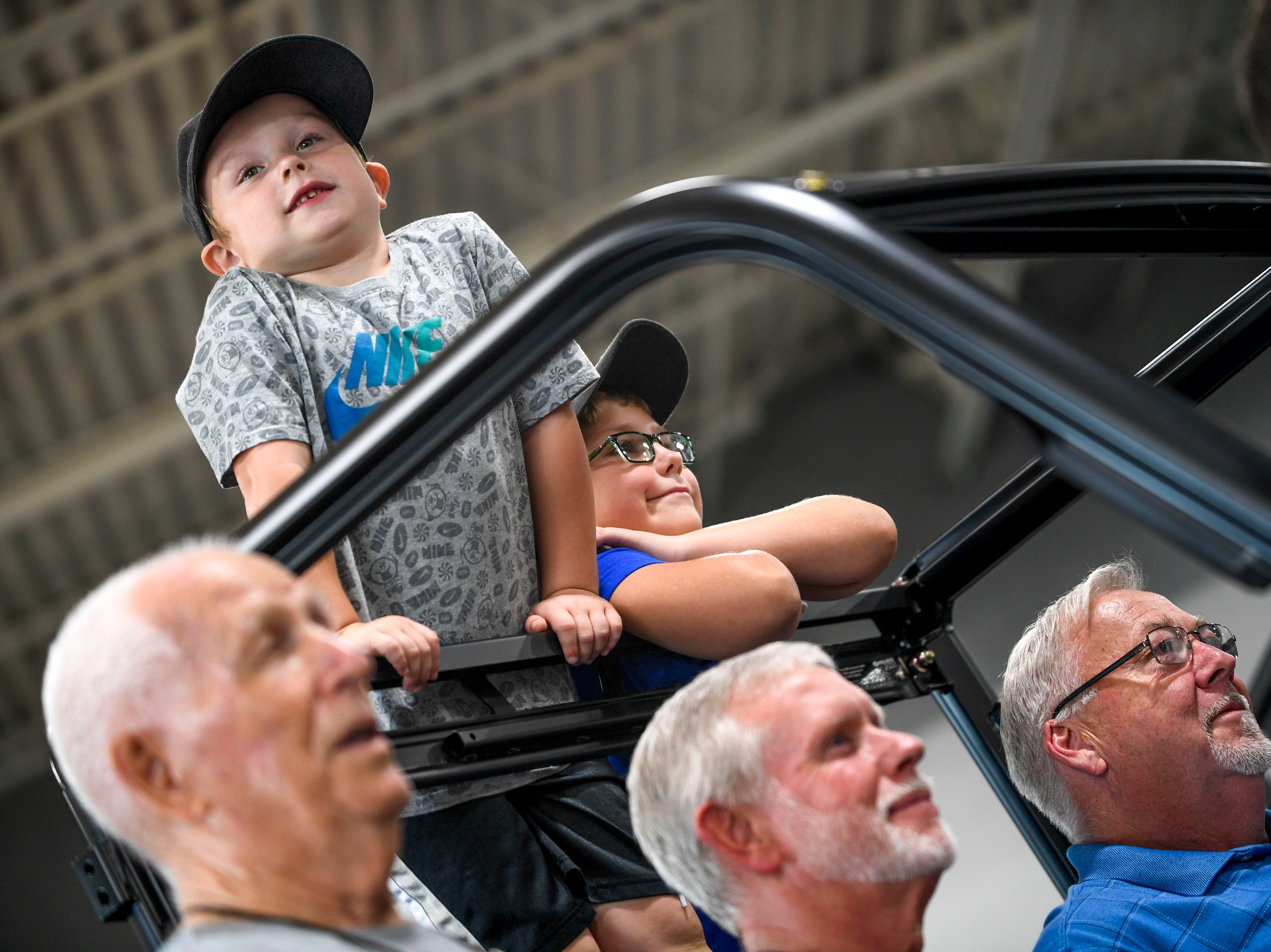 John Patrick Coleman, 4, and his brother Bradley Coleman, 8, right, prop themselves up on the roll cage of a Polaris Ranger their grandfather John Coleman, bottom right corner, won in a contest at Bob's House of Honda in Jackson, Tenn., on Thursday, Sept. 20, 2018.