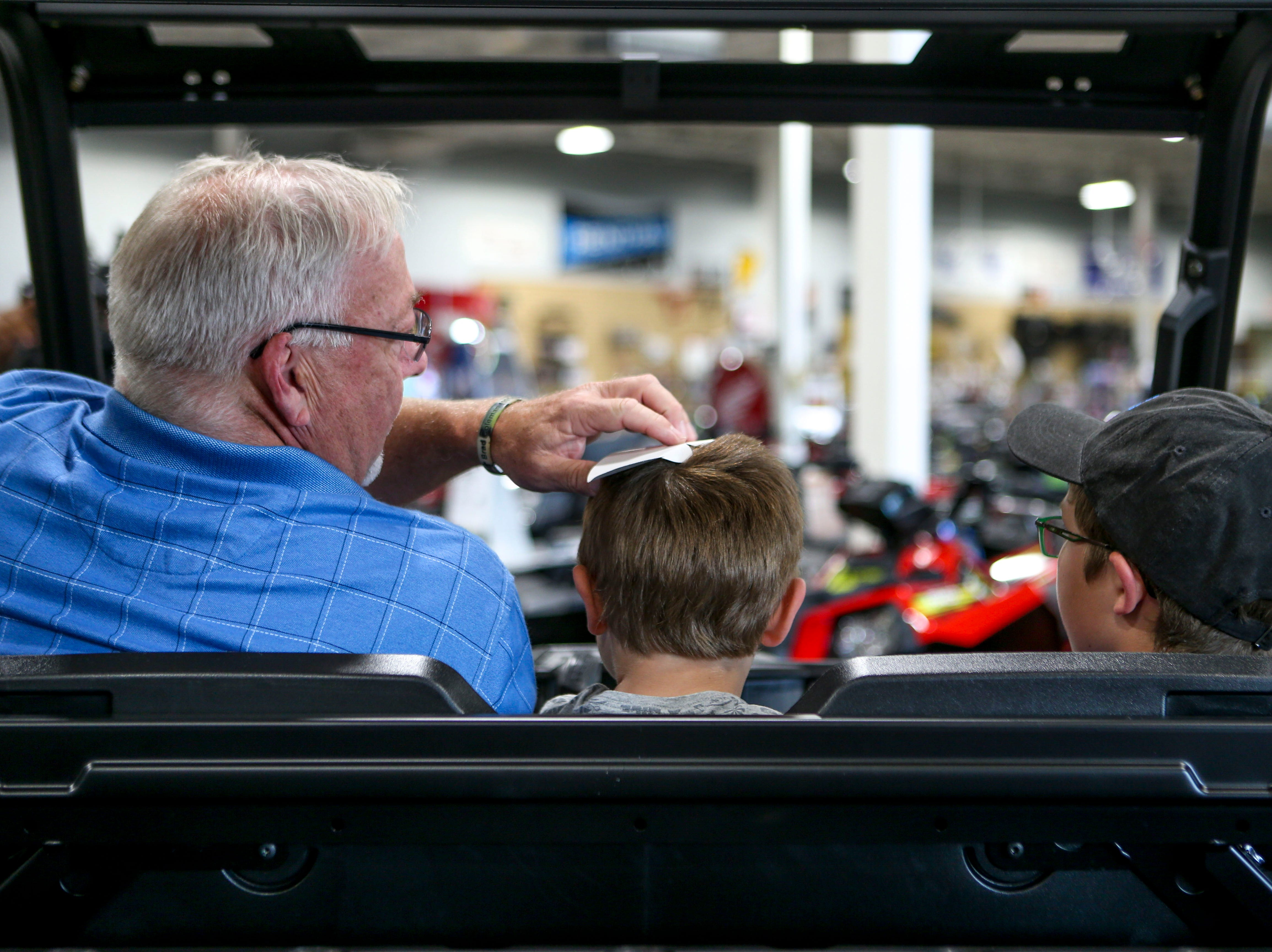 John Coleman, left, pulls off a piece of paper from a baseball hat that John Patrick Coleman, 4, center, placed on his head at Bob's House of Honda in Jackson, Tenn., on Thursday, Sept. 20, 2018.