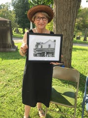 Friends of the Library president Rusha Sams holds a picture of Mary U. Rothrock and one of her bookmobiles.