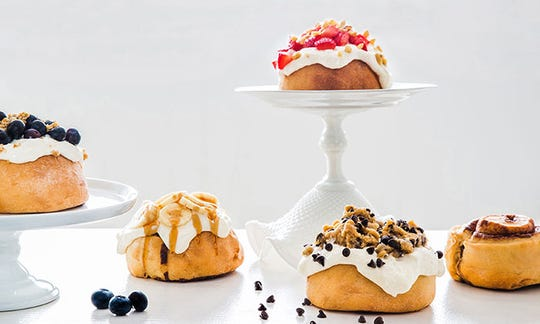 """Cinnaholic vegan cinnamon roll creations include blueberry pie crumble, banana chai caramel, strawberry graham cracker, cookie dough with chips and chocolate sauce, and the """"old school"""" roll."""