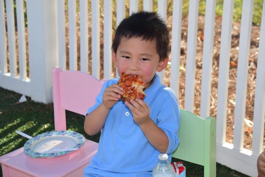 Isaac Wang, 4, takes a bite out of his slice of pizza at a 10th Anniversary Birthday Bash held at The Goddard School Saturday, Sept. 15.