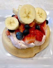Cinnaholic mini vegan cinnamon roll topped with raspberry frosting and fresh fruit