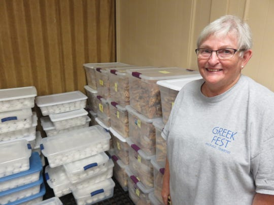 Church volunteer Sharon Alexander stands next to some of the baked items being stored before being sold during Greekfest.