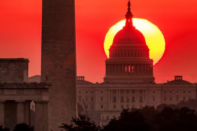 The sun rises behind the U.S. Capitol in Washington at dawn Wednesday, Sept. 19. 2018. (AP Photo/J. David Ake)