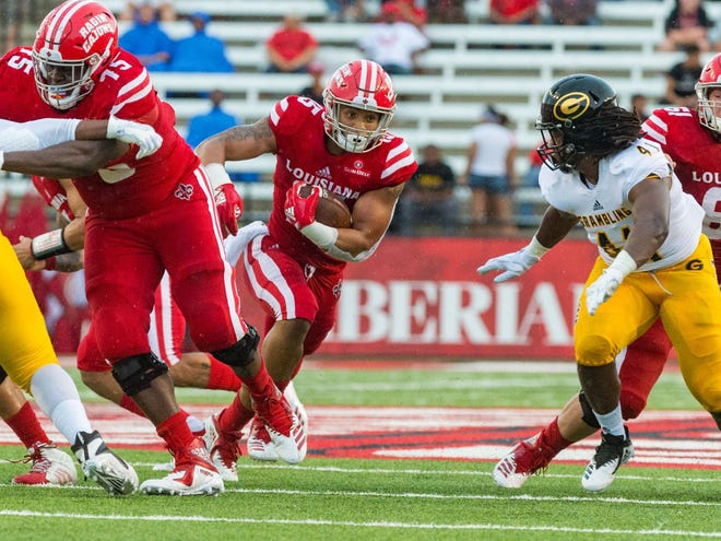 With Kevin Dotson (75) blocking, UL's Elijah Mitchell picks up some yards against Grambling earlier this season.