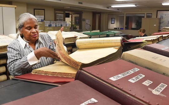 Marie Marcel looks over voter registration records from the 1800s in the St. Landry Parish Courthouse.
