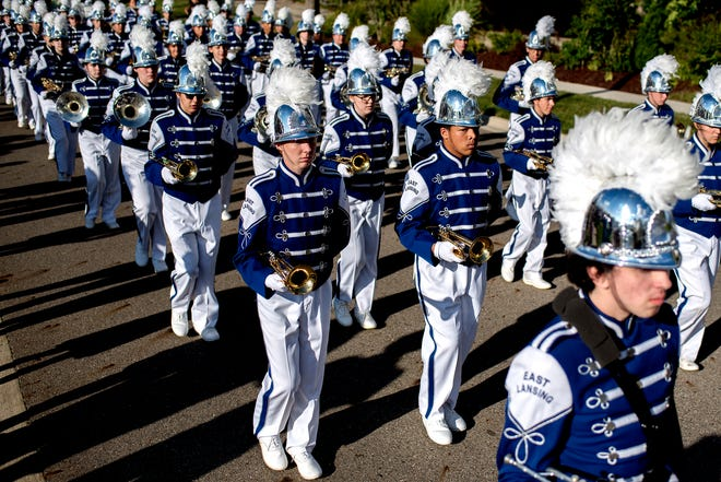 Members of the East Lansing High School marching band lead off the homecoming parade before the Trojans' football game against DeWitt outside the stadium on Friday, Sept. 21, 2018, in East Lansing.