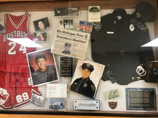 A memorial to fallen Manitowoc Police Officer Dale TenHaken hangs in the Oostburg High School.