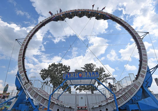 Fairgoers are suspended upside down Friday afternoon as they ride the Fire Ball at the Ashland County Fair.