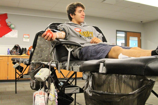 Mason Stefanka squeezes a stress ball during a blood drive at Elgin High School Friday morning.