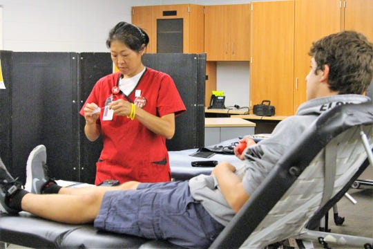 Red Cross phlebotomist Vincy Tsang helps donor Mason Stefanka during a blood drive at Elgin High School on Friday. Approximately 14,000 donations are needed every day to keep the blood supply at a sufficient level.