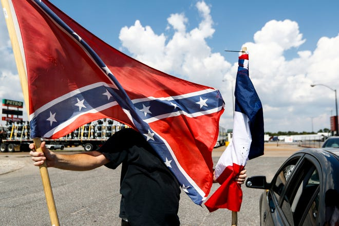 """September 21 2018 - George """"K-rack"""" Johnson changes out flags on his car in West Memphis, Arkansas before traveling to Memphis with the Confederate 901 group . The group is upset over the removal of statues of Confederate President Jefferson Davis and Gen. Nathan Bedford Forrest from Memphis parks in December and the July 28 removal of additional memorabilia."""