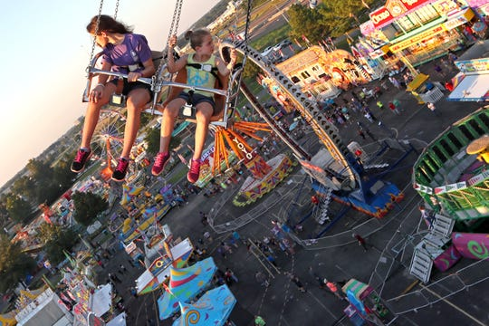Sisters Heidi Brann, 13, and Ainsley, 9, ride the swing chairs on opening day of the Mid-South Fair at the Landers Center in DeSoto County, Mississippi on Thursday, Sept. 20, 2018.