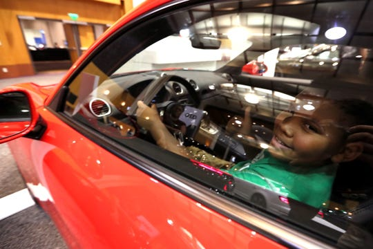 Donovan Owens, 11, sits down behind the wheel of a Porsche Cayman GT during the 2019 Model Year Memphis International Auto Show the Cook Convention Center Friday, Sept. 21, 2018.