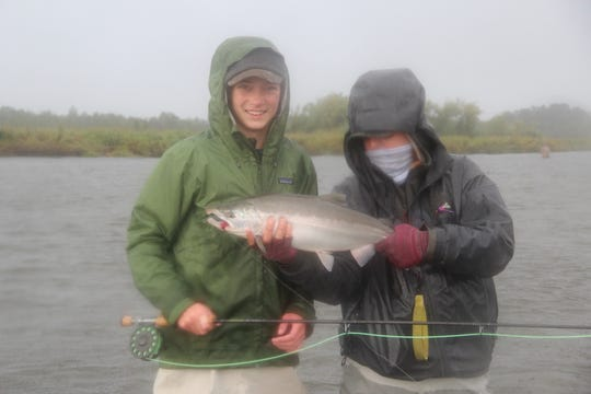 Cormac Moss, left, of Eau Claire, Wisconsin caught and released this silver salmon on the Alagnak River in Alaska.