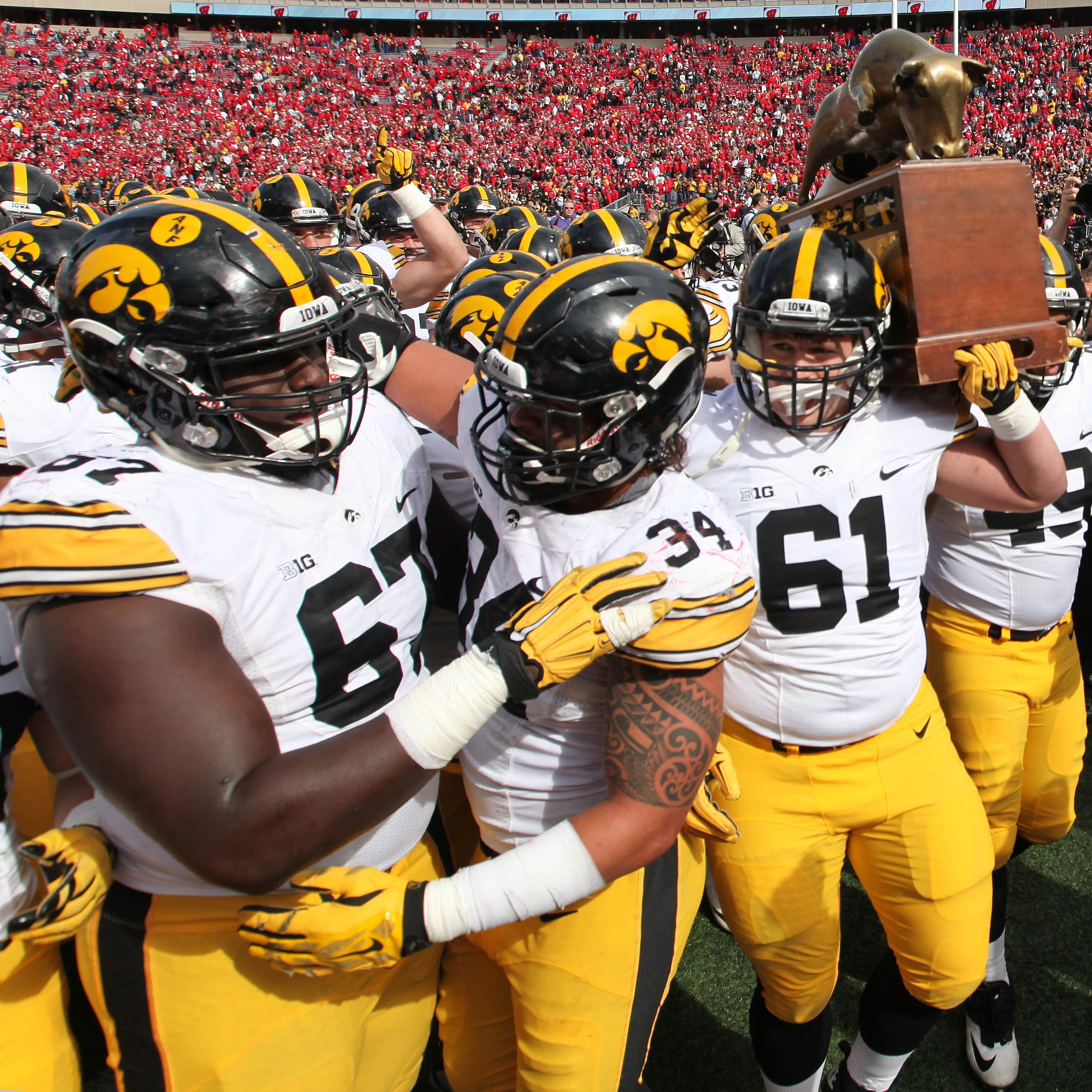 The Iowa Hawkeyes carry the Heartland trophy off...