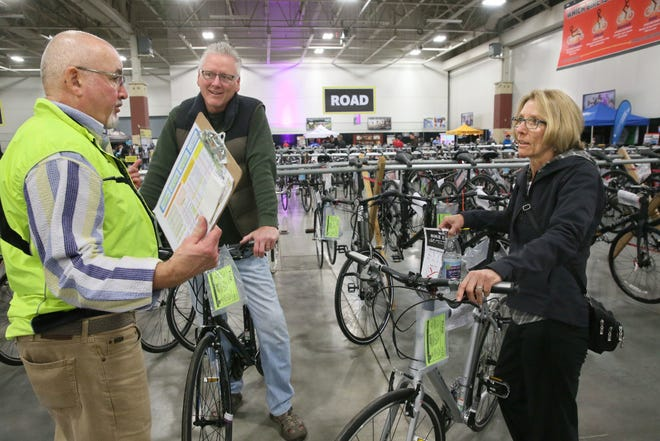 Steve Ikeler of Wheel & Sprocket in Hales Corners (left) helps Jeff and Linda Davis of Brookfield find a pair of new bikes last year at Wheel & Sprocket's annual bike expo at State Fair Park. Retail prices for bicycles could go up under tariffs on Chinese-made bikes for companies like Trek Bicycle Corp.