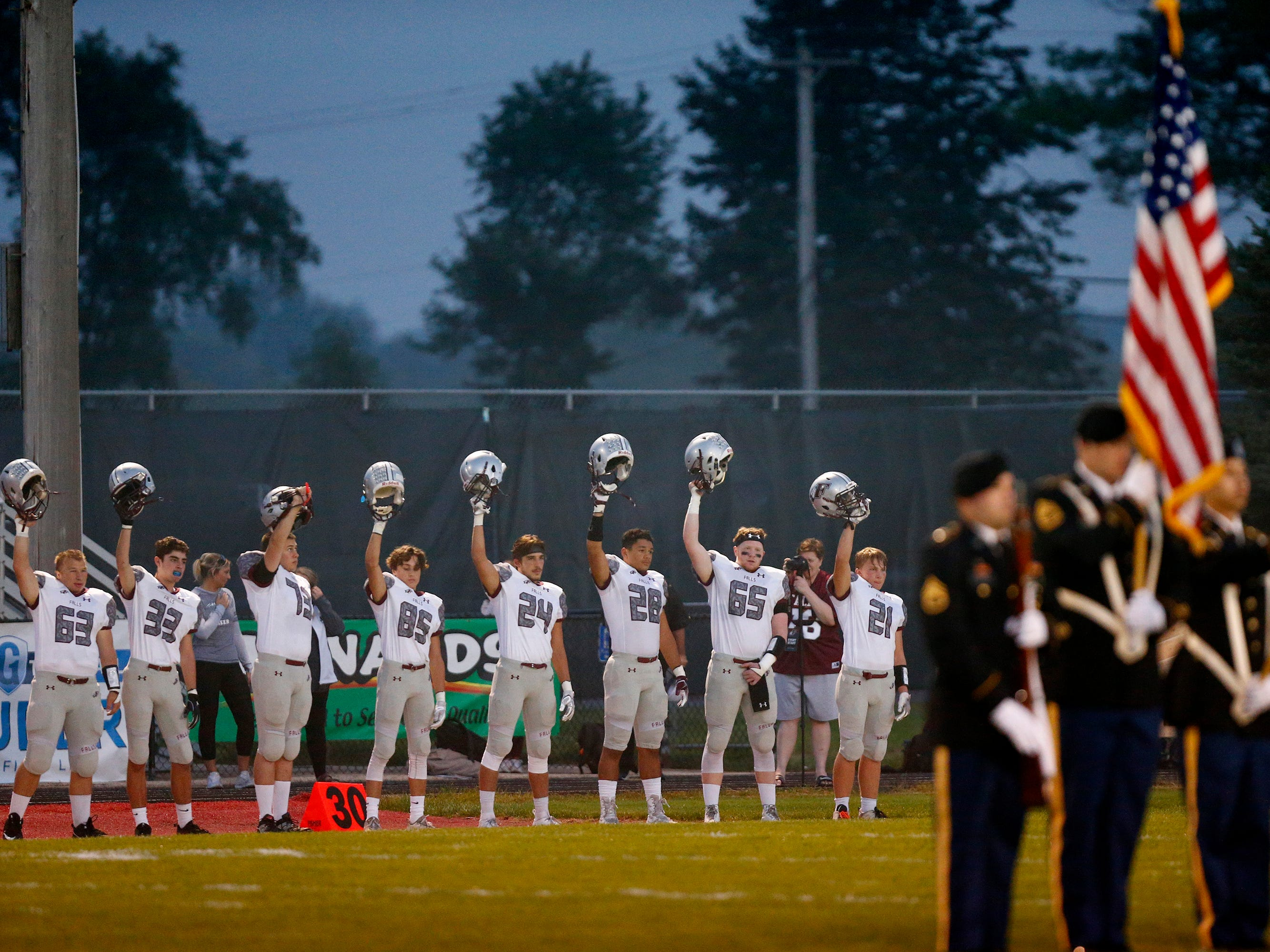Menomonee Falls players raise their helmets at the end of the national anthem before the start of the game Sept. 20 at Sussex Hamilton.