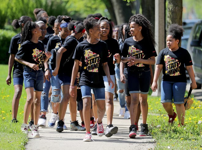 Some of the 2,000 Milwaukee College Prep students march down Sherman Boulevard in May 2018 to celebrate the school's 20th anniversary.