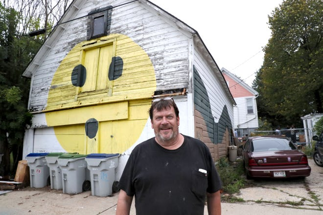 Steve Swetlik stands in the alley in front of the face he painted several years ago on an old hayloft barn behind his home on Buffum Street in Milwaukee. Swetlik has lost the property in a city tax foreclosure, and the fate of the barn is unclear.