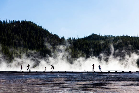 Tourists walk around the Grand Prismatic Hot Spring at Yellowstone National Park's Midway Geyser Basin in Wyoming on Tuesday, Sept. 4, 2018.