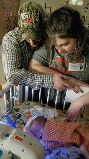 Brandon and Krystal Grumm look over their son, Braydon, in his hospital bed.