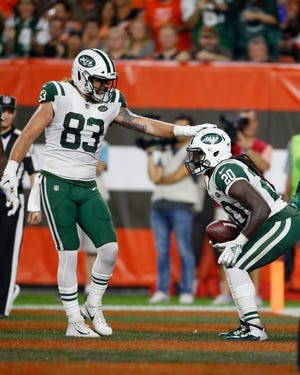 New York Jets tight end Eric Tomlinson (83) congratulates running back Isaiah Crowell (20) after Crowell ran for a two-yard touchdown during the first half of an NFL football game against the Cleveland Browns, Thursday, Sept. 20, 2018, in Cleveland.