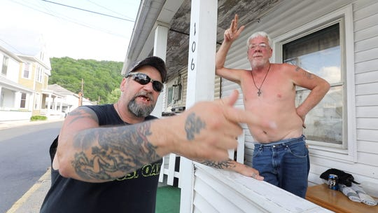 Timothy McCusker Sr., left, and Danny McCarty, both of whom are unemployed, outside McCarty's home in Keyser. The 1½-bedroom apartment rents for $450 per month.