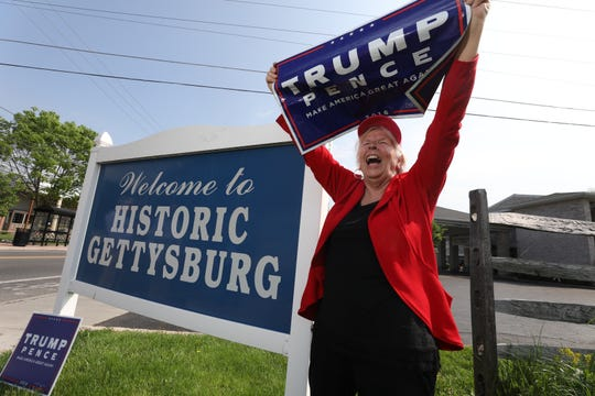 """Elizabeth """"Betsy"""" Hower, chair of the Adams County Republican Committee shows off her Trump signs that she had gotten at the 2016 Republican convention at the entrance to the town of Gettysburg, the Adams county seat."""
