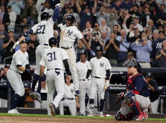 New York Yankees' Giancarlo Stanton (27) celebrates with teammates Aaron Judge, Aaron Hicks (31) and Didi Gregorius after hitting a grand slam during the fourth inning of a baseball game Thursday, Sept. 20, 2018, in New York. At right is Boston Red Sox catcher Christian Vazquez.