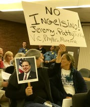 Resident Stacey Gregg holds a sign at a Sept. 20 meeting to illustrate her frustration with Rockaway Township Council's voting majority who made John Inglesino the township attorney.