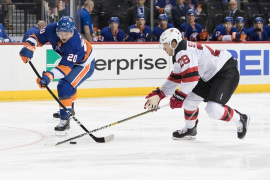New York Islanders left wing Kieffer Bellows (20) and New Jersey Devils defenseman Damon Severson (28) vie for the puck during the second period of a preseason NHL hockey game, Thursday, Sept. 20, 2018, in New York.