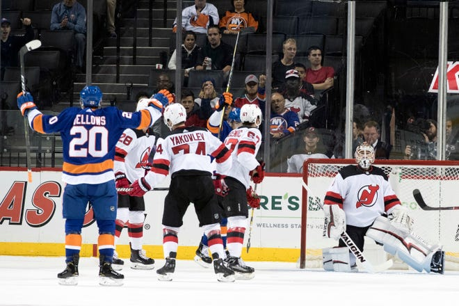 New York Islanders left wing Kieffer Bellows (20) and New Jersey Devils goalie Keith Kinkaid, right, react after Bellows scored a goal during the first period of an NHL hockey game, Thursday, Sept. 20, 2018, in New York.