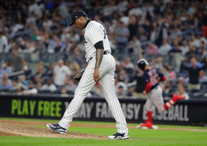 New York Yankees relief pitcher Aroldis Chapman walks up the mound as Boston Red Sox's Mookie Betts runs the bases after hitting a three-run home run during the eighth inning of a baseball game Thursday, Sept. 20, 2018, in New York.
