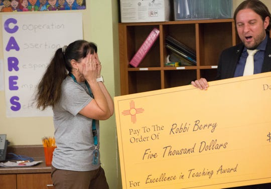 Christopher Ruszkowski, New Mexico education secretary-designate, presents a shocked Robbi Berry with a check for $5,000 which is part of an the Excellence in Teaching Award, in front of her fourth-grade class Friday September 21, 2018 at Monte Vista Elementary School.