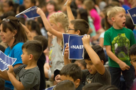"""Children from five different Las Cruces area schools wave National Assessment of Educational Progress signs, handed out at the end of a presentation where those schools celebrated getting """"A"""" grades from the Public Education Department."""