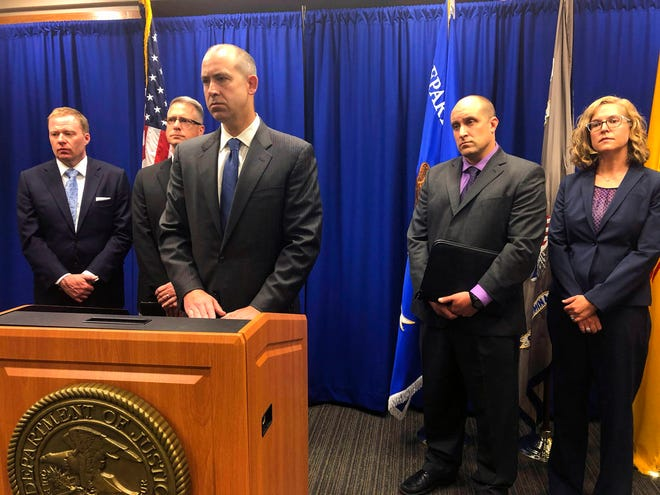 U.S. Attorney John Anderson, center at podium, speaks about the investigation into a fugitive Catholic priest who is accused of sex abuse at a news conference Friday, Sept. 21, 2018, in Albuquerque, N.M. Federal authorities said FBI agents returned 80-year-old Arthur Perrault to New Mexico on Friday to face child sexual abuse charges after a year in the custody of Moroccan authorities.