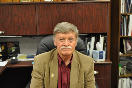 Dr. John Gratton sitting in his office at New Mexico State University Carlsbad.