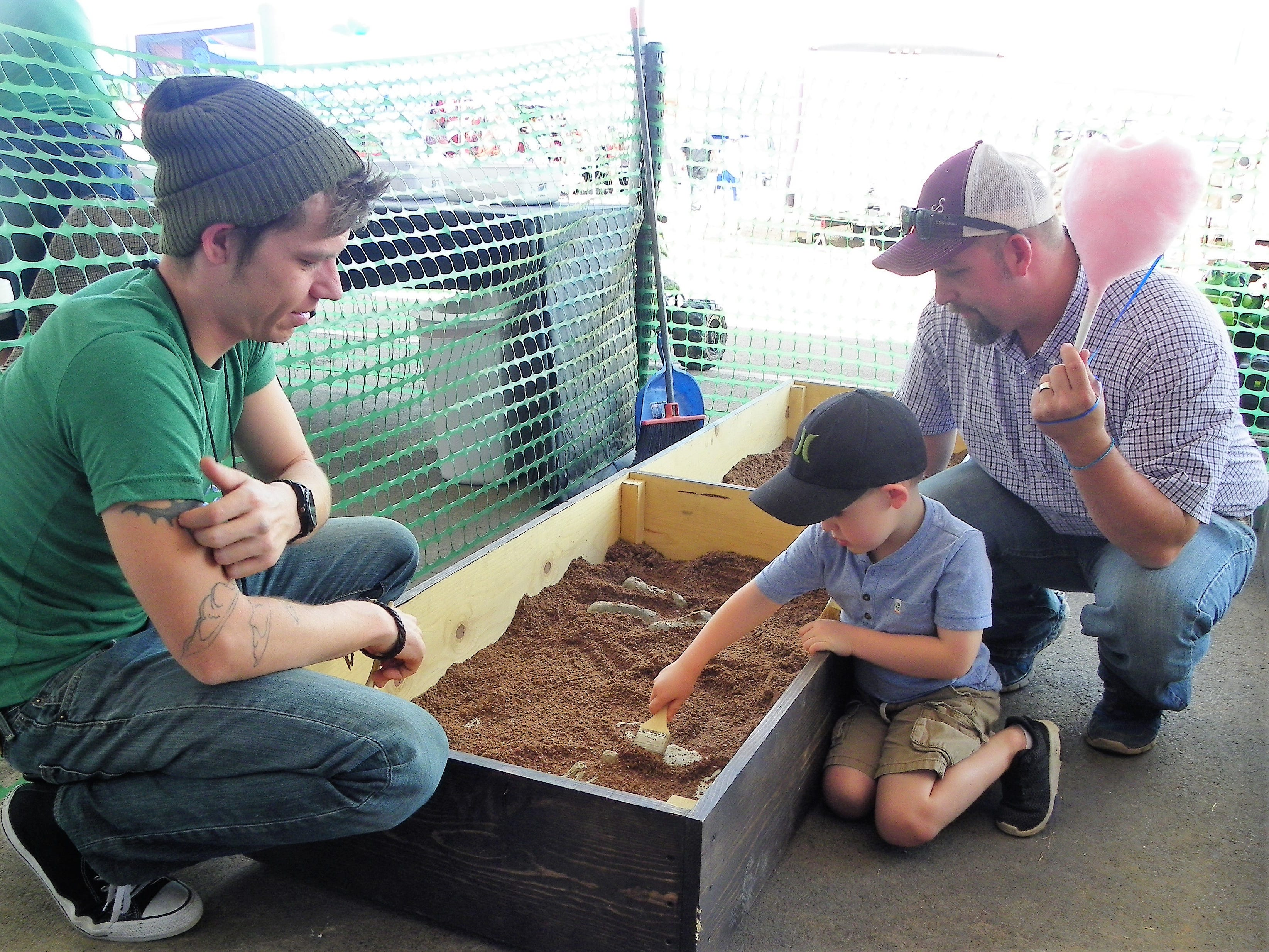 Tony Case, center, digs for dinosaur bones at the Otero County Fair Friday as Robert Posey, left, and Chase Montes, watch.
